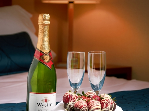 Champagne and Chocolate Strawberries on Bed